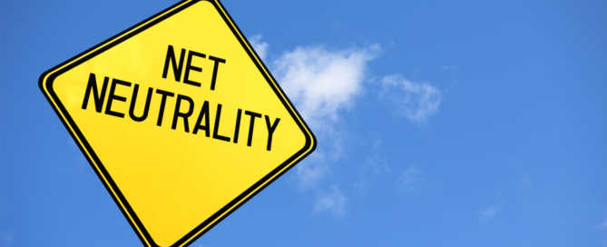 """A yellow warning sign with the text """"Net Neutrality"""" against a blue sky."""